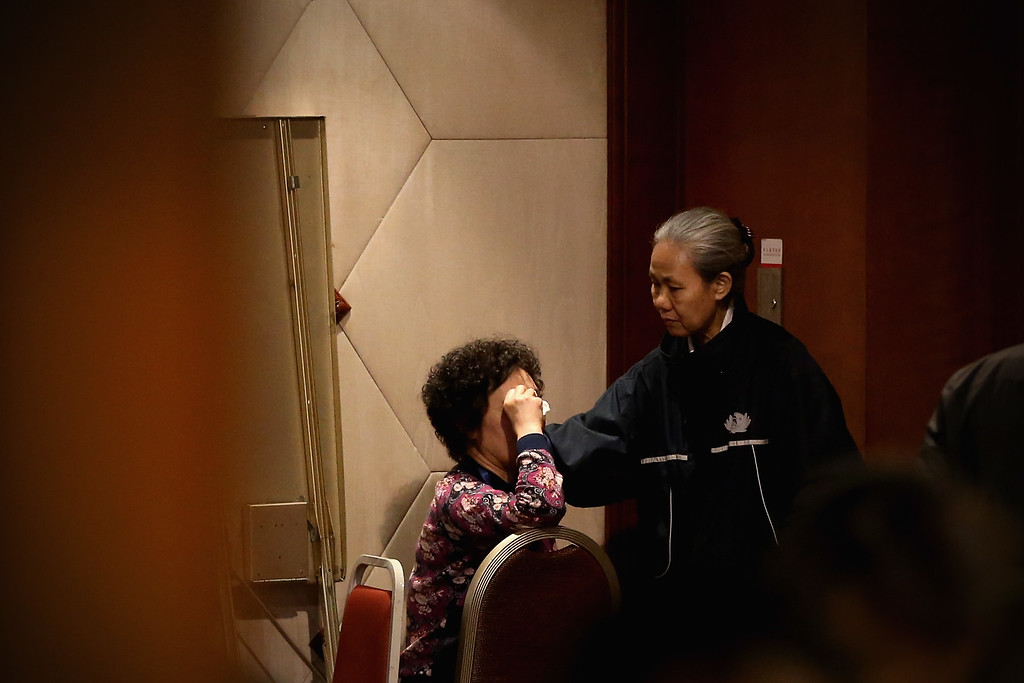 Description of . A charity worker comforts an emotional relative of a passenger onboard the Malaysia Airlines flight MH370 as families of the missing line up to receive a special condolence payment of 31,000 CNY (almost 5,000 USD) at Lido Hotel on March 12, 2014 in Beijing, China.  (Photo by Feng Li/Getty Images)