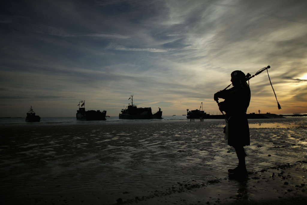 Description of . A piper plays a lament on Gold Beach as landing craft from the Royal Marines arrive at Arromanche on June 6, 2014 in Arromanches Les Bains, France.    (Photo by Christopher Furlong/Getty Images)
