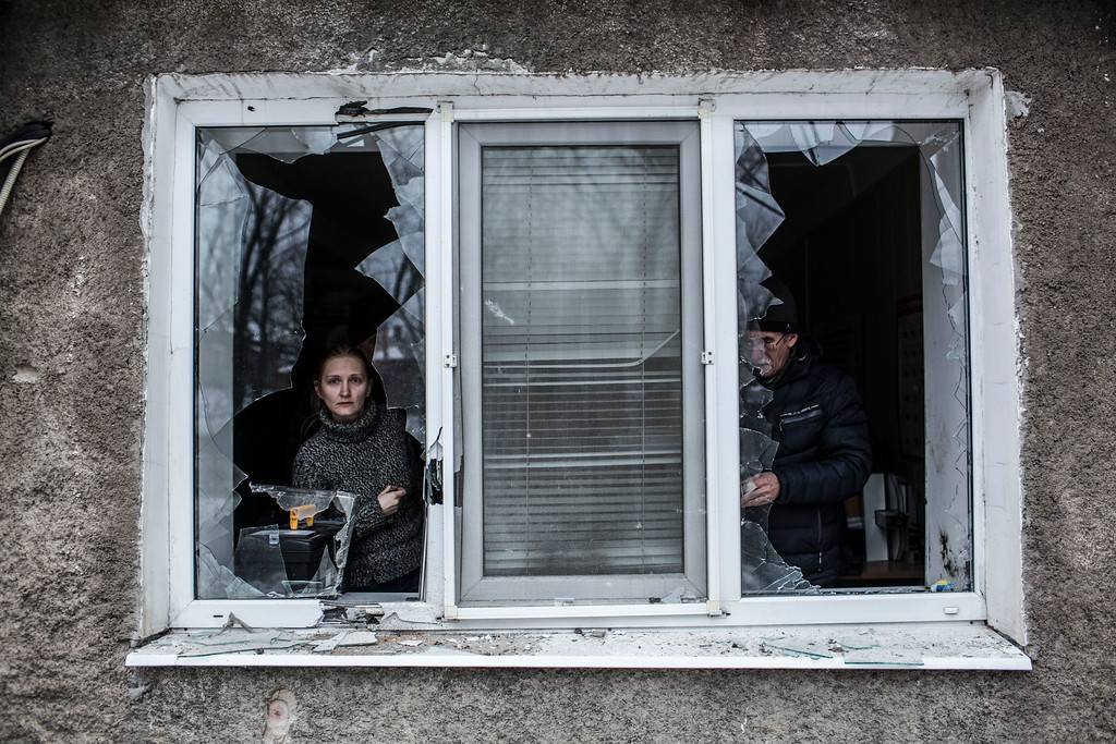Description of . A Ukrainian woman looks through a broken window at their flat after it was hit by Ukrainian Artillery in the Voroshilovsky area, center of Donetsk, Ukraine. Sunday, Jan. 18, 2015. The separatist stronghold, Donetsk, was shaken by intense outgoing and incoming artillery fire as a bitter battle raged for control over the city's airport. Streets in the city, which was home to 1 million people before unrest erupted in spring, were completely deserted and the windows of apartments in the center rattled from incessant rocket and mortar fire. (AP Photo/Manu Brabo)