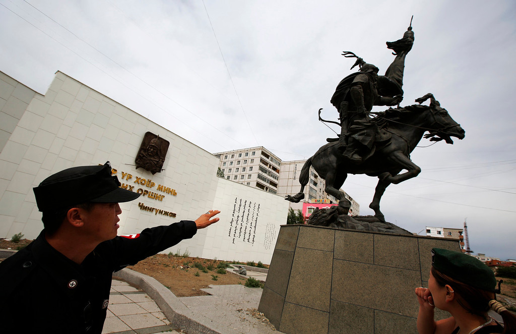 Description of . Ariunbold (L) and Uranjargal, leaders of the Mongolian neo-Nazi group Tsagaan Khass, stand next to a statue of Chingunjav, a Mongolian national hero, in Ulan Bator June 22, 2013. The group has rebranded itself as an environmentalist organisation fighting pollution by foreign-owned mines, seeking legitimacy as it sends Swastika-wearing members to check mining permits. Over the past years, ultra-nationalist groups have expanded in the country and among those garnering attention is Tsagaan Khass, which has recently shifted its focus from activities such as attacks on women it accuses of consorting with foreign men to environmental issues, with the stated goal of protecting Mongolia from foreign mining interests. This ultra-nationalist group was founded in the 1990s and currently has 100-plus members. Picture taken June 22, 2013. REUTERS/Carlos Barria