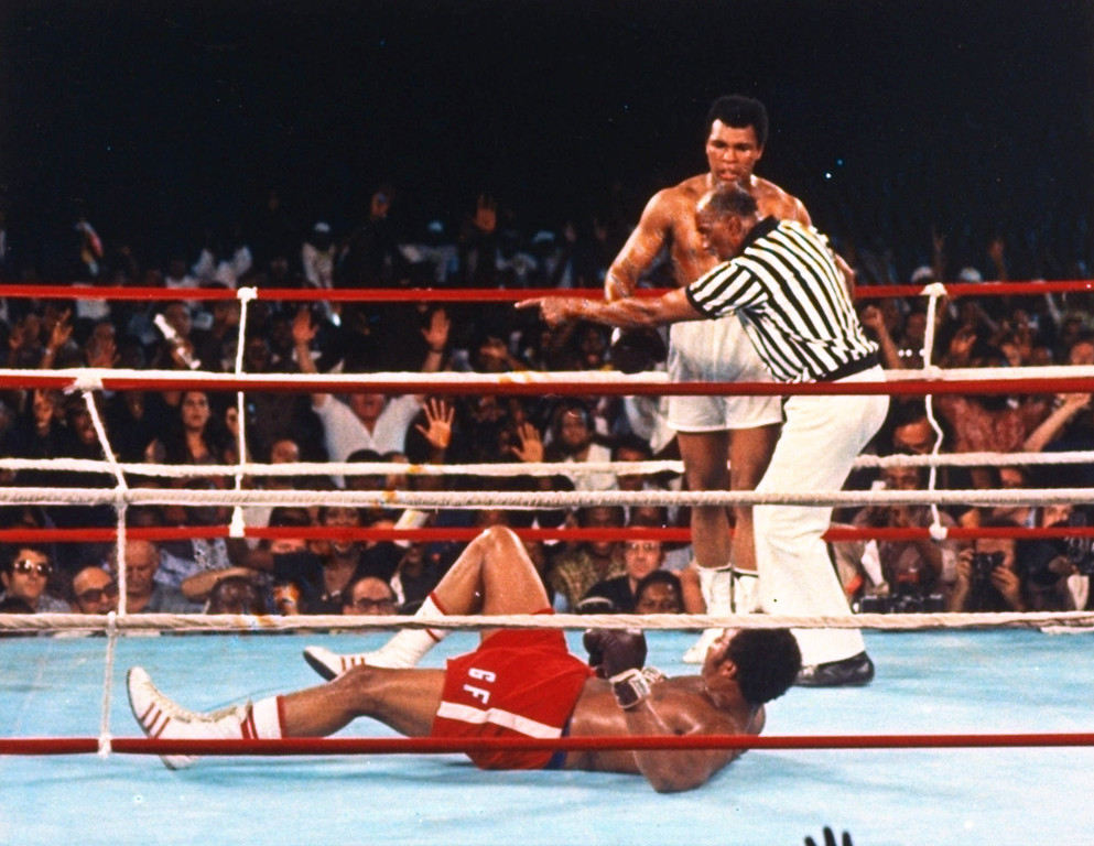 Description of . Challenger Muhammad Ali is directed to a neutral corner by referee Zack Clayton after knocking down George Foreman and ending their title fight in the eighth round, in Kinshasa, Zaire, in this Oct. 29, 1974 photo. (AP Photo/File)