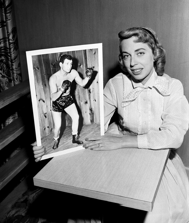 . Dr. Joyce brothers, child Psychologist who won the $64,000 jackpot in quiz on boxing knowledge is shown with a photo of boxer James J. Parker, July 22, 1956. (AP Photo)
