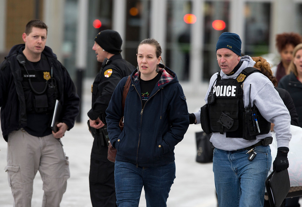Description of . Police and law enforcement evacuate The Mall of Columbia after a shooting Saturday, Jan. 25, 2014, in Columbia, Md. Police say three people died in a shooting at the mall in suburban Baltimore, including the presumed gunman. (AP Photo/ Evan Vucci)