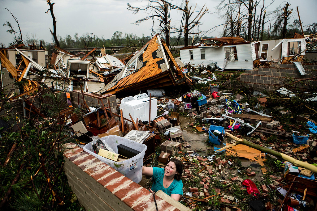 Description of . Jodi Walls pushes a box of belongings out of a friends house while cleaning up after a large tornado made its way along Clayton Ave in Tupelo, Miss., Monday, April 28, 2014. (AP Photo/The Commercial Appeal, Brad Vest)