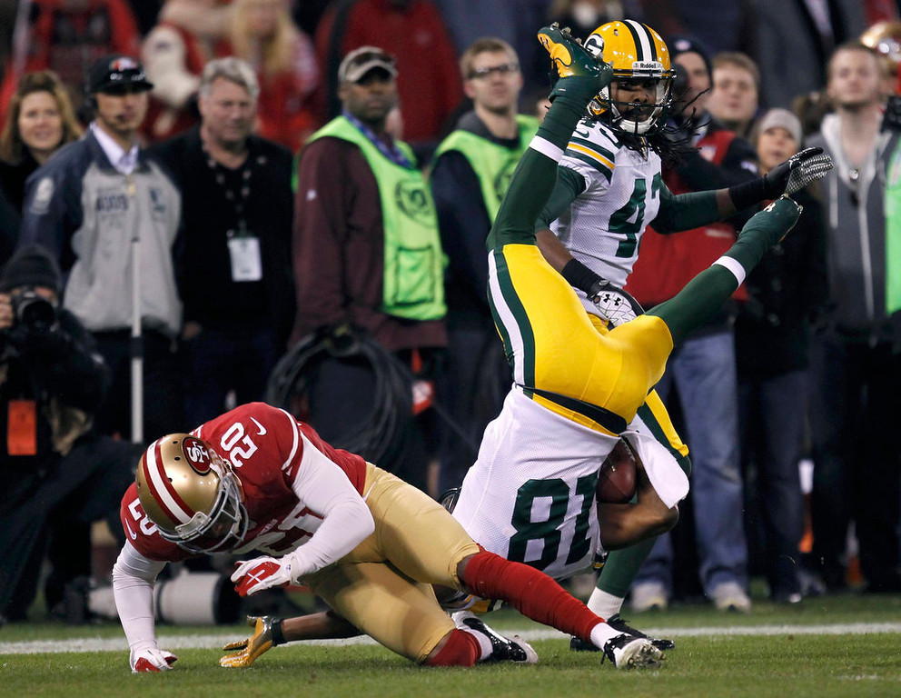 Description of . Green Bay Packers Randall Cobb (C) is tackled by San Francisco 49ers Perrish Cox (L) next to Packers M.D. Jennings (R) in the second quarter during their NFL NFC Divisional playoff football game in San Francisco, California, January 12, 2013.  REUTERS/Robert Galbraith