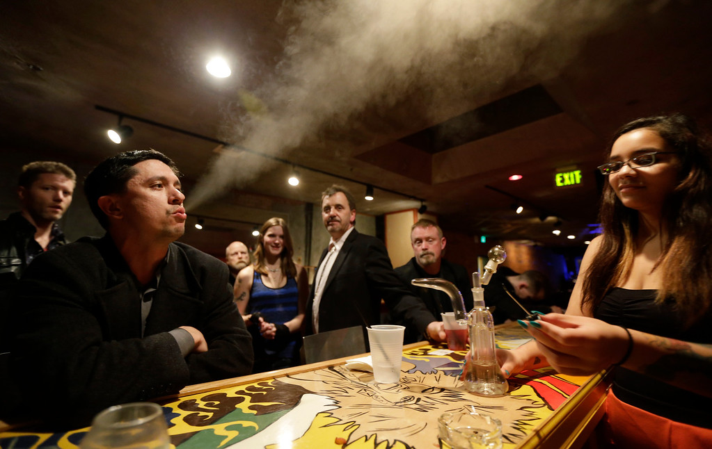 Description of . John Connelly, left, exhales after inhaling marijuana vapor just after midnight Saturday, March 2, 2013, with the help of bar worker Jenae DeCampo, right, in the upstairs lounge area of Stonegate, a pizza-and-rum bar in Tacoma, Wash. Owner Jeff Call charges patrons a small fee to become a member of the private second-floor club, which prohibits smoking marijuana, but does permit
