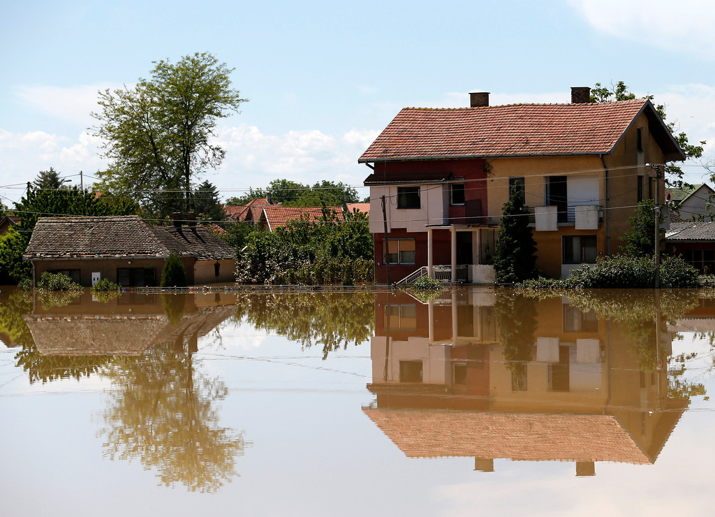Description of . Houses reflected in a flooded street in Obrenovac, some 30 kilometers (18 miles) southwest of Belgrade, Serbia, Monday, May 19, 2014. Belgrade braced for a river surge Monday that threatened to inundate Serbia's main power plant and cause major power cuts in the crisis-stricken country as the Balkans struggle with the consequences of the worst flooding in southeastern Europe in more than a century.  (AP Photo/Darko Vojinovic)