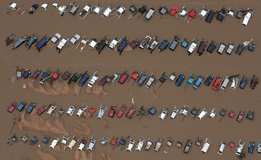 Description of . Cars in a junk yard on 37th Street in Evans,  Colorado, are surrounded by mud and flood waters from the Platte River in Weld County on Monday, September 16, 2013. The flood has devastated cities and farms throughout the county as well as elsewhere in the state. (Photo By Tim Rasmussen/The Denver Post)