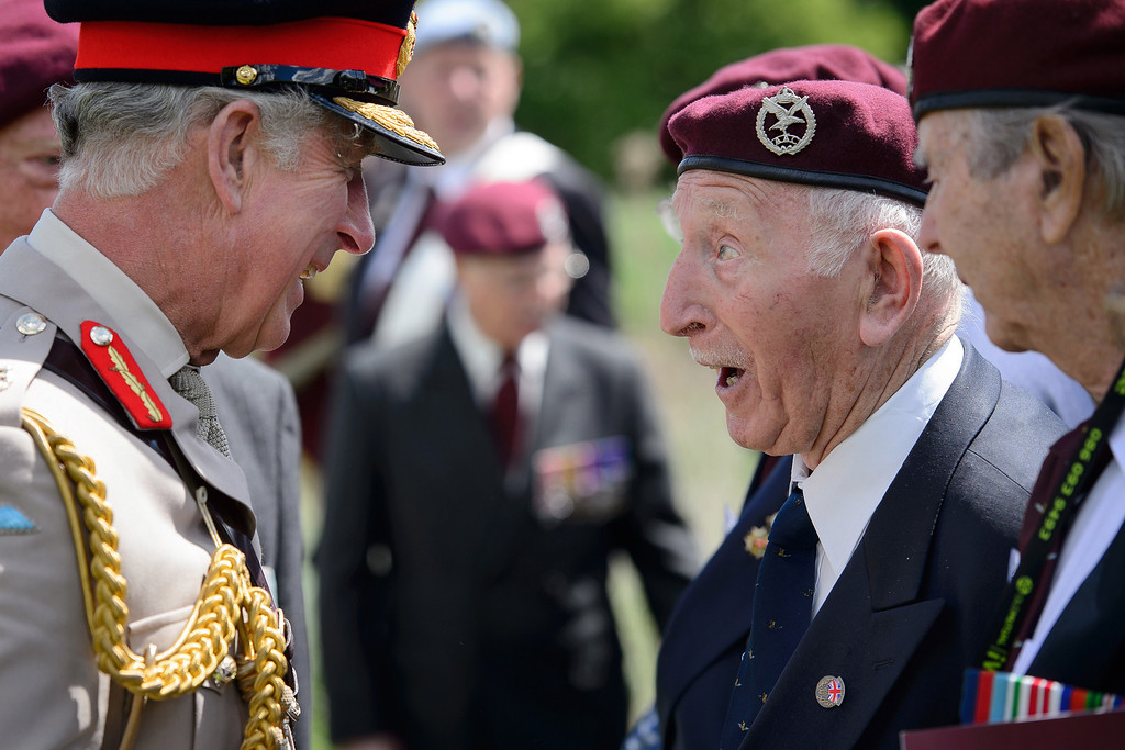 Description of . Britain's Prince Charles, left, meets British glider pilot World War II veterans during a D-Day commemoration event at the Pegasus bridge, in Benouville, western France, Thursday, June 5, 2014, marking the 70th anniversary of the World War II Allied landings in Normandy. June 6, 2014 marks the 70th anniversary of D-Day and
