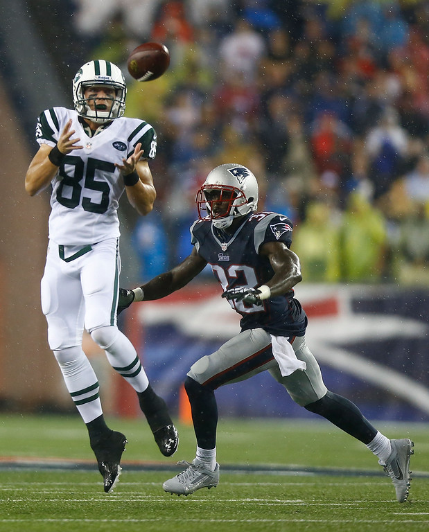 Description of . Ryan Spadola #85 of the New York Jets attempts to catch a pass in front of Devin McCourty #32 of the New England Patriots before having it knocked out of his hands during the game at Gillette Stadium on September 12, 2013 in Foxboro, Massachusetts. (Photo by Jared Wickerham/Getty Images)
