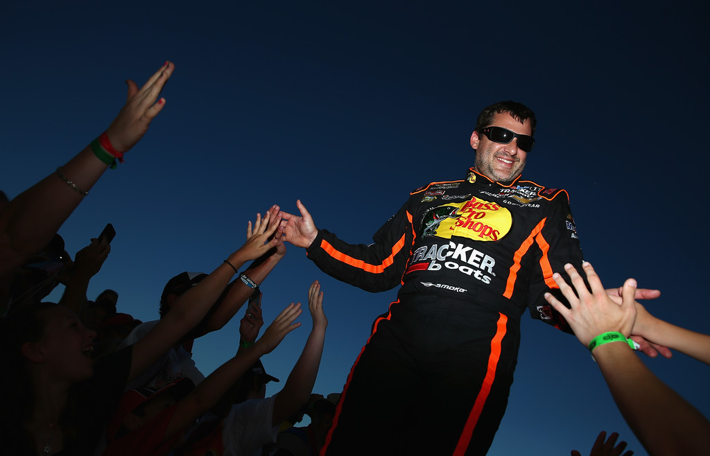 Description of . DAYTONA BEACH, FL - JULY 06:  Tony Stewart, driver of the #14 Bass Pro Shops / Ducks Unlimited Chevrolet, greets fans during driver introductions during the NASCAR Sprint Cup Series Coke Zero 400 at Daytona International Speedway on July 6, 2013 in Daytona Beach, Florida.  (Photo by Tom Pennington/Getty Images)