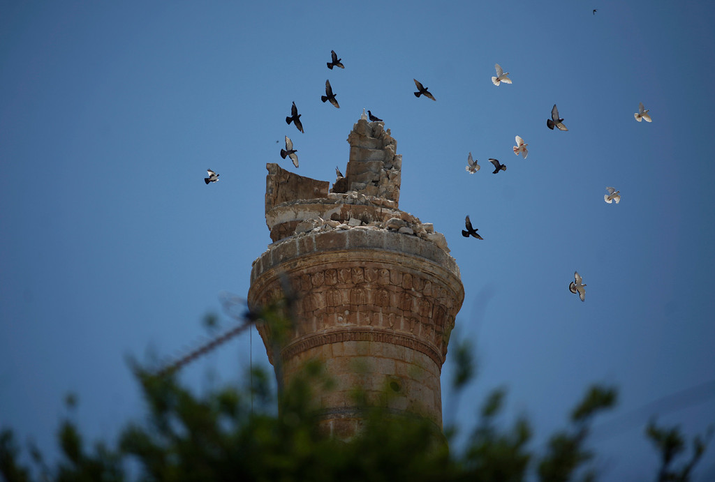 Description of . FILE - Birds fly over the destroyed minaret of a mosque in the northern town of Ariha, on the outskirts of Idlib, Syria, Sunday, June 10, 2012. (AP Photo/Khalil Hamra, File)