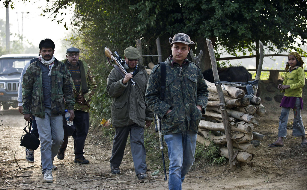 Description of . Indian marksman Nawab Shafat Ali Khan (2R) patrols with his team as they search for a tiger in the forest near the village of Barahpur in Bijnor District some 120kms north-east of New Delhi on February 2, 2014.  Since December 29, 2013, the same tiger is believed to have killed eight people living near the national park which covers 521 square kilometers in the northern states of Uttar Pradesh and Uttarakhand.  PRAKASH SINGH/AFP/Getty Images