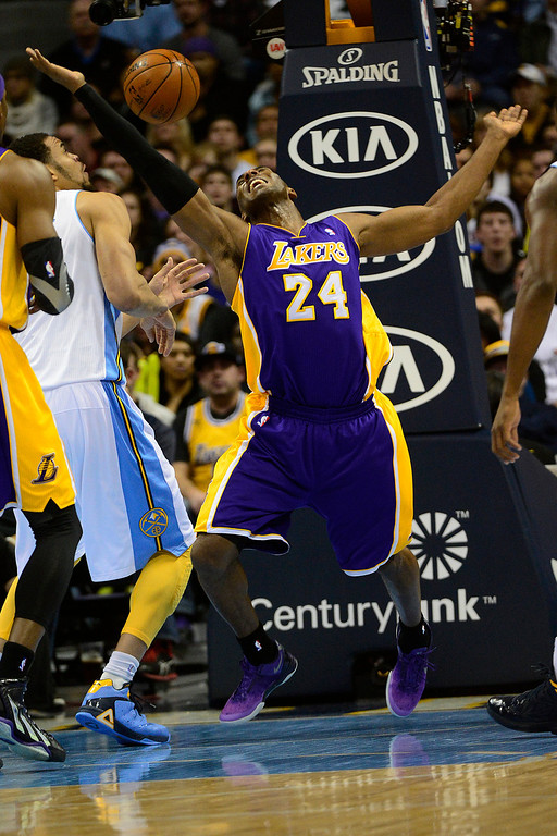 Description of . Los Angeles Lakers shooting guard Kobe Bryant (24) gets fouled by Denver Nuggets shooting guard Andre Iguodala (9) during the first half at the Pepsi Center on Wednesday, December 26, 2012. AAron Ontiveroz, The Denver Post