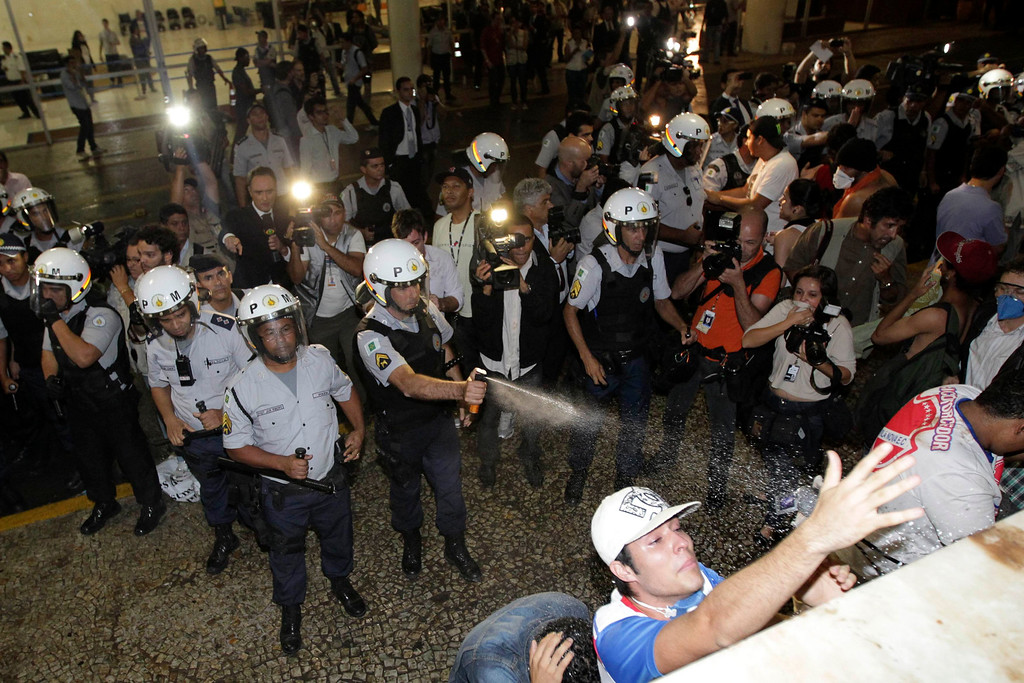 Description of . A police officer uses pepper spray on demonstrators protesting against the Confederation's Cup and the government of Brazil's President Dilma Rousseff outside the national congress in Brasilia June 17, 2013. Tens of thousands of demonstrators marched through the streets of Brazil's biggest cities on Monday in a growing protest that is tapping into widespread anger at poor public services, police violence and government corruption. Protesters are using the Confederation's Cup as a counterpoint to amplify their concerns.  REUTERS/Ueslei Marcelino