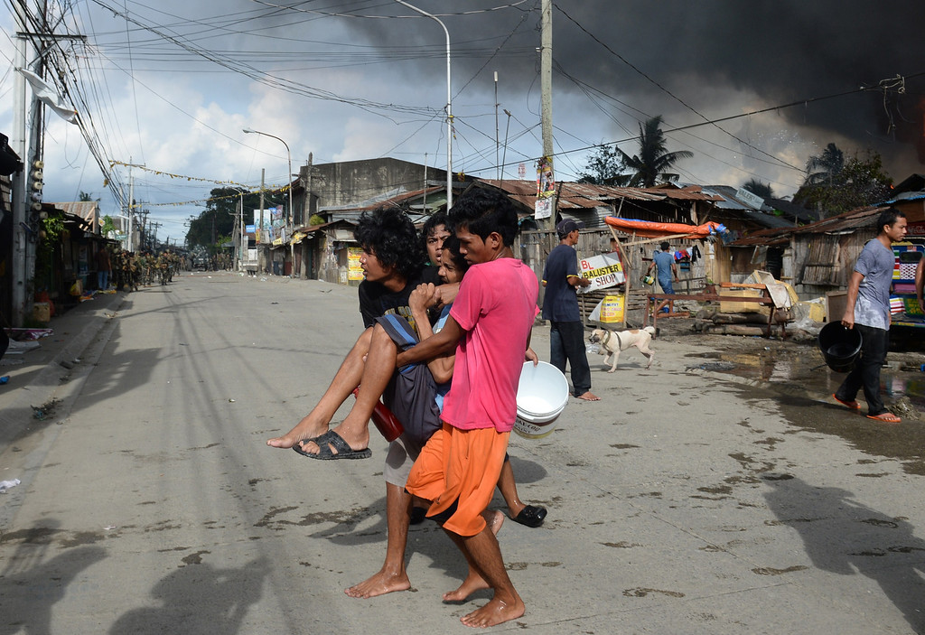 Description of . A sick resident is evacuated from burning houses during a fire fight between government forces and Muslim rebels as stand-off entered its fourth day in Zamboanga City on the southern island of Mindanao on September 12, 2013. AFP PHOTO/TED ALJIBE/AFP/Getty Images