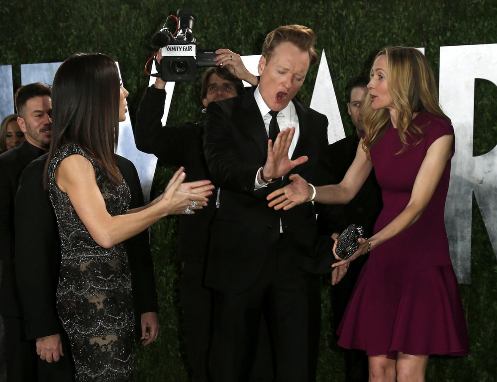 Description of . Sandra Bullock (L), Conan O'Brien and wife Liza Joke (R) around before posing on the carpet at the 2013 Vanity Fair Oscars Party in West Hollywood, California February 24, 2013.  REUTERS/Danny Moloshok