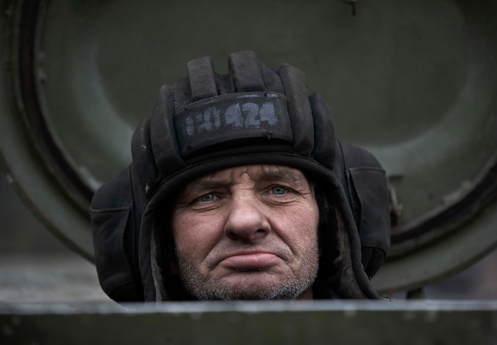 Description of . A Russia-backed separatist fighter sits in a self propelled 152 mm artillery piece, part of a unit moved away from the front lines, in Yelenovka, near Donetsk, Ukraine,Thursday, Feb. 26, 2015. Russia\'s foreign minister is sharply criticizing Ukraine\'s insistence that it won\'t begin pulling back heavy weapons in its fight against separatists in the east until the rebels fully observe a cease-fire. (AP Photo/Vadim Ghirda)