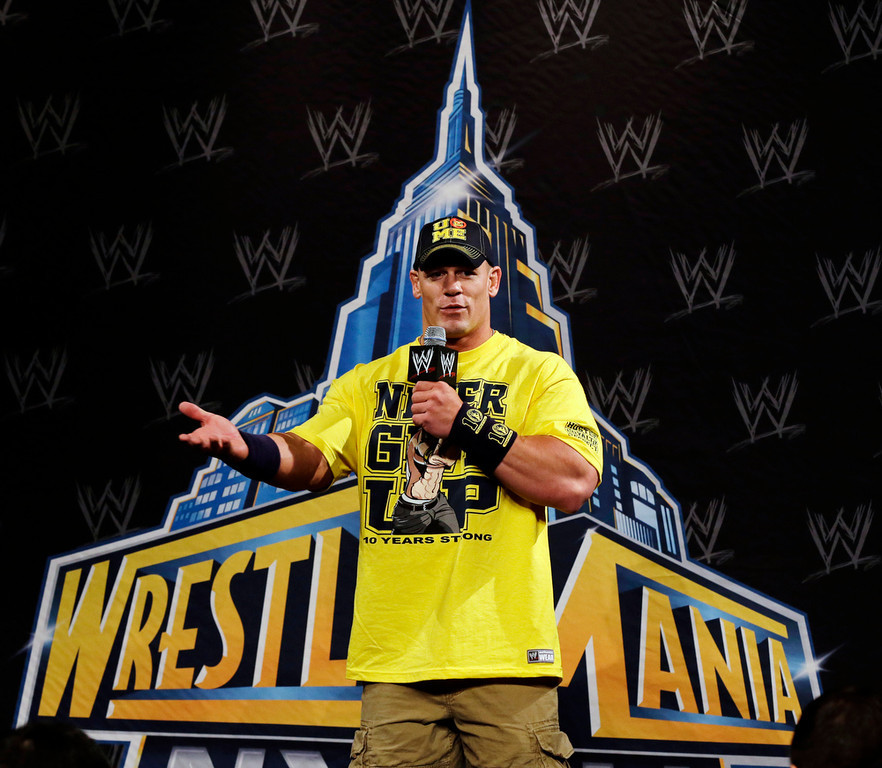 Description of . John Cena answers a question during a news conference before the WWE Wrestlemania 29 wrestling event, Sunday, April 7, 2013, in East Rutherford, N.J. (AP Photo/Mel Evans)