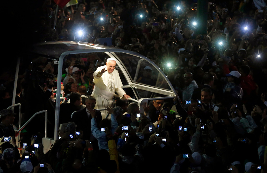 Description of . Pope Francis arrives for a World Youth Day celebration at the Copacabana beachfront in Rio de Janeiro, Brazil, Thursday July 25, 2013. Cheering pilgrims from 175 nations lined the beachfront drive to catch a glimpse of Francis. The popemobile stopped several times for Francis to kiss babies - and take a sip of his beloved mate, the traditional Argentine tea served in a gourd with a straw, that was handed up to him by someone in the crowd. (AP Photo/Enric Marti)