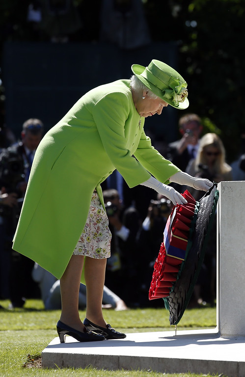Description of . Queen Elizabeth II lays a wreath at the foot of the Cross of Sacrifice in the centre of Commonwealth War Graves Commission Cemetery during a service of remembrance on June 6, 2014 in Bayeux, France.  (Photo by Jonathan Brady - Pool/Getty Images)