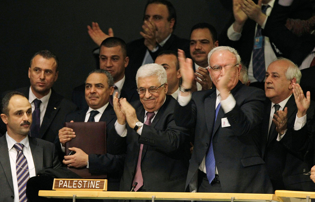. In this Nov. 29, 2012 file photo, members of the Palestinian delegation react as they surround Palestinian President Mahmoud Abbas, center, applauding, during a meeting of the United Nations General Assembly after a vote on a resolution on the issue of upgrading the Palestinian Authority\'s status to non-member observer state passed in the United Nations in New York.  (AP Photo/Kathy Willens, File)