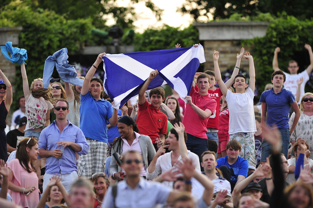 Description of . Tennis fans hold up a Scottish flag as they watch on the big screen at Murray Mount Britain\'s Andy Murray play against Poland\'s Jerzy Janowicz in their men\'s singles semi-final match on day eleven of the 2013 Wimbledon Championships tennis tournament at the All England Club in Wimbledon, southwest London, on July 5, 2013. GLYN KIRK/AFP/Getty Images