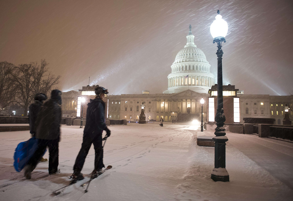 Description of . A young man on skis and his friends pass in front of the US Congress building as a heavy snow storm hits Washington D.C. on February 13, 2014. The eastern US, in the grips of one of the most brutal winters in recent memory, braced for what forecasters warned could be the worst broadside yet -- a massive storm with the season\'s heaviest snowfall. AFP PHOTO / MLADEN ANTONOV/AFP/Getty Images