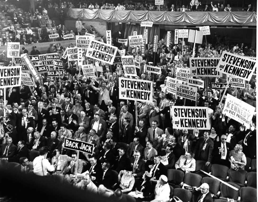 Description of . Delegates hoist signs and stand up as the name of Sen. John F. Kennedy of Massachusetts is placed before the Democratic Convention on Aug. 17, 1956, as a possible vice presidential nominee.  Associated Press file