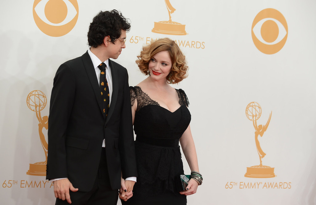 Description of . Geoffrey Arend, left, and Christina Hendricks arrive at the 65th Primetime Emmy Awards at Nokia Theatre on Sunday Sept. 22, 2013, in Los Angeles.  (Photo by Jordan Strauss/Invision/AP)