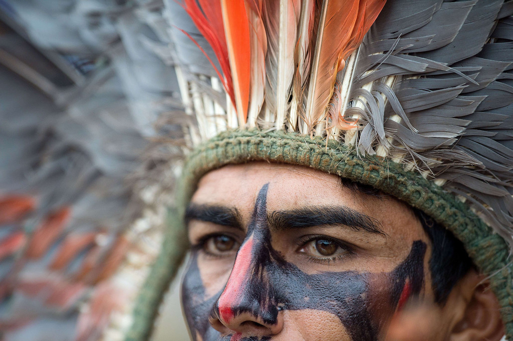Description of . A Brazilian indigenous man of the Terena tribe observes the bow and arrow competition during the XII International Games of Indigenous Peoples in Cuiaba, Mato Grosso state, Brazil on November 12, 2013.  AFP PHOTO / Christophe SIMON/AFP/Getty Images