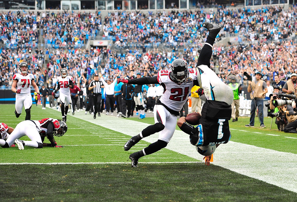 . CHARLOTTE, NC - DECEMBER 09:  Cam Newton #1 of the Carolina Panthers dives into the end zone for a touchdown in front of defender Christopher Owens #21 f the Atlanta Falcons  during play at Bank of America Stadium on December 9, 2012 in Charlotte, North Carolina.  (Photo by Grant Halverson/Getty Images)