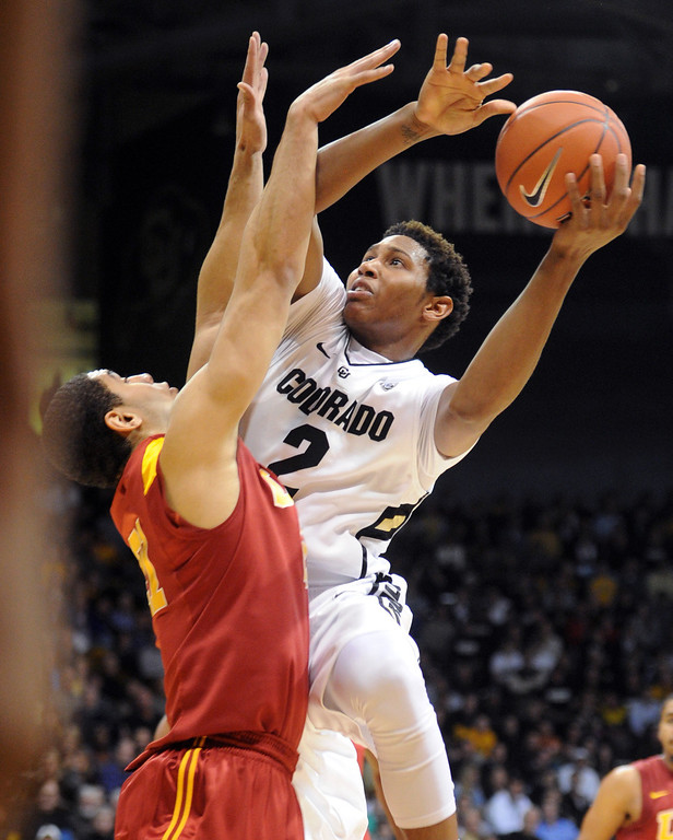 Description of . Xavier Johnson of Colorado goes to the basket on Aaron Fuller of Southern California during the first half of the January 10, 2013 game in Boulder.  Cliff Grassmick/Daily Camera