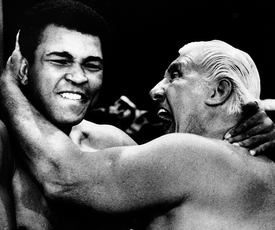 Description of . Professional wrestler Freddy Blassie, right, is shown tangling with boxing legend Muhammad Ali while filming a promotion at an arena in Philadelphia on June 1, 1976. (AP Photo/File)