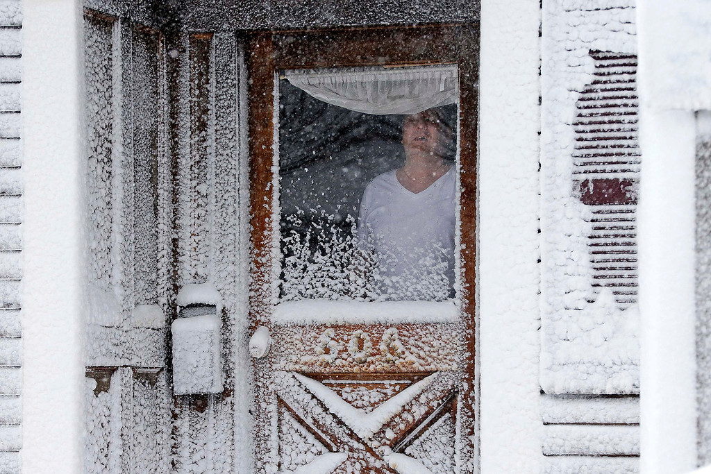 . A resident of Third Street in the South Boston neighborhood of Boston looks out of his snow-coated front door Saturday, Feb. 9, 2013. A behemoth storm packing hurricane-force wind gusts and blizzard conditions swept through the Northeast overnight. (AP Photo/Gene J. Puskar)