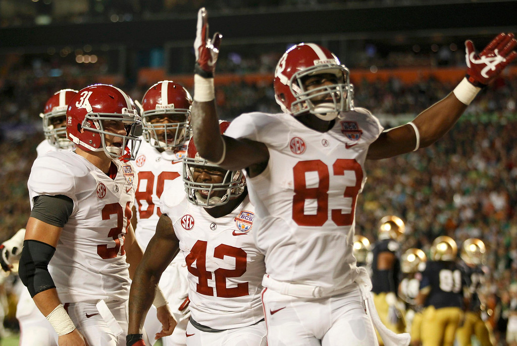 Description of . Alabama Crimson Tide's Eddie Lacy (C) celebrates with teammates Kevin Norwood (R) and Jerrod Bierbower (L) after scoring a touchdown against the Notre Dame Fighting Irish in the first quarter of their NCAA BCS National Championship college football game in Miami, Florida January 7, 2013. REUTERS/Jeff Haynes