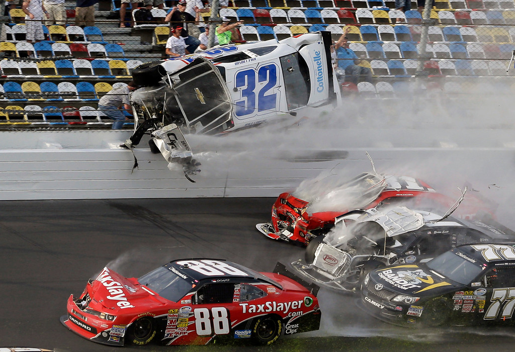 Description of . Kyle Larson (32) goes airborne and into the catch fence in a multi-car crash involving Dale Earnhardt Jr. (88), Parker Kilgerman (77), Justin Allgaier (31) and Brian Scott (2) during the final lap of the NASCAR Nationwide Series auto race at Daytona International Speedway, Saturday, Feb. 23, 2013, in Daytona Beach, Fla. (AP Photo/John Raoux)