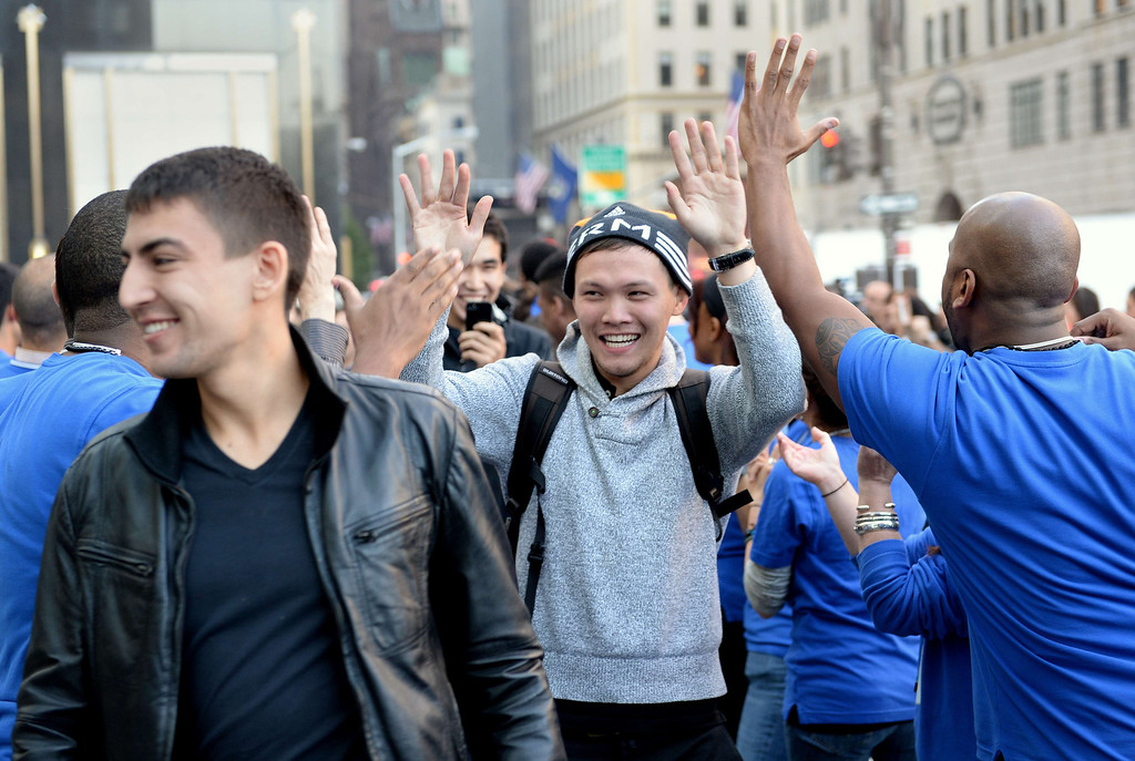 Description of . Customers waiting to buy the Apple iPhone 5 are greeted by employees at the Apple Store on Fifth Avenue September 20, 2013 in New York. Some waited as long as fifteen days in line outside the store to be the first to buy the phone. AFP PHOTO/Stan HONDA/AFP/Getty Images