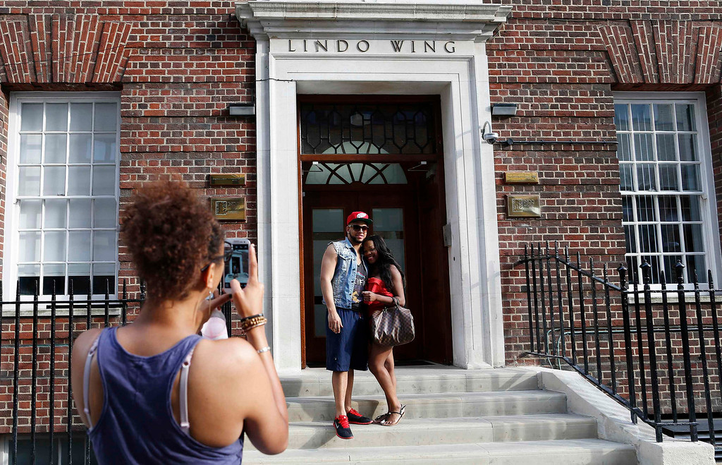 Description of . Members of the public take photos in front of the Lindo Wing of St Mary\'s Hospital, where Britain\'s Catherine, Duchess of Cambridge, is due to give birth in Paddington, London, July 14, 2013.  REUTERS/Olivia Harris