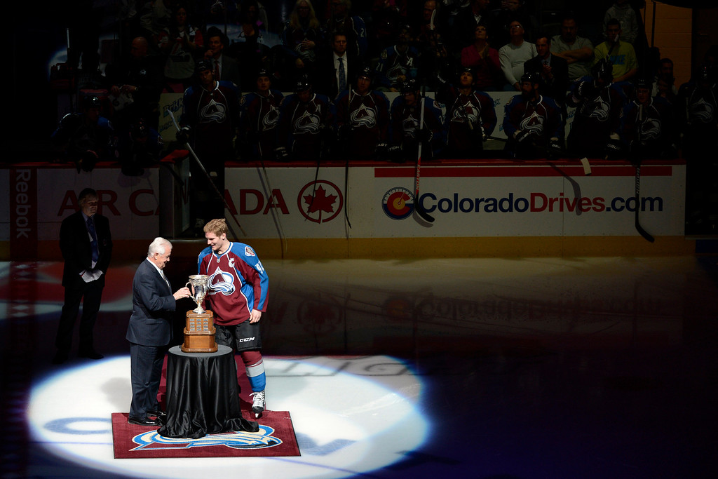 Description of . DENVER, CO. - JANUARY 22: Colorado Avalanche left wing Gabriel Landeskog (92) accepts the Calder Memorial Trophy for NHL Rookie of the Year from retired NHL player Ralph Backstrom before the first period. The Colorado Avalanche hosted the Los Angeles Kings at the Pepsi Center on January, 22, 2013.    (Photo By John Leyba / The Denver Post)