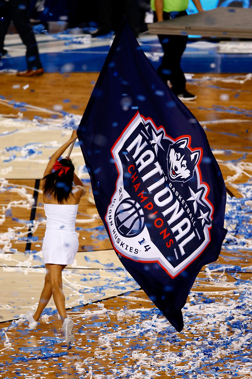 Description of . ARLINGTON, TX - APRIL 07: A Connecticut Huskies cheerleader walks on the court after defeating the Kentucky Wildcats 60-54 in the NCAA Men\'s Final Four Championship at AT&T Stadium on April 7, 2014 in Arlington, Texas.  (Photo by Tom Pennington/Getty Images)