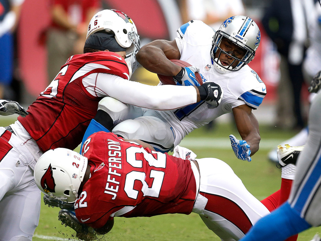 Description of . Arizona Cardinals defensive end Ronald Talley (96) loses his helmet as he tackles Detroit Lions running back Reggie Bush (21) as Arizona Cardinals defensive back Tony Jefferson (22) assists during the first half of a NFL football game, Sunday, Sept. 15, 2013, in Glendale, Ariz. (AP Photo/Darryl Webb)