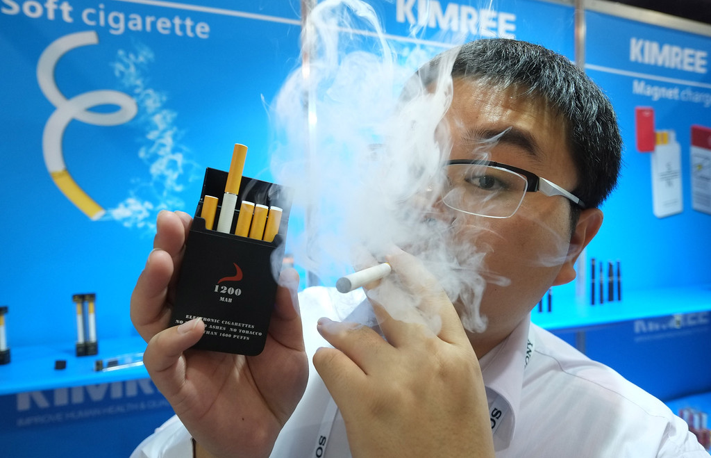 Description of . Bin Zhou of Kimree shows electronic cigarettes at the Kimree booth during the 2014 International CES at the Las Vegas Convention Center on January 8, 2014 in Las Vegas, Nevada. CES, the world's largest annual consumer technology trade show, runs through January 10 and is expected to feature 3,200 exhibitors showing off their latest products and services to about 150,000 attendees. AFP PHOTO/JOE KLAMAR/AFP/Getty Images