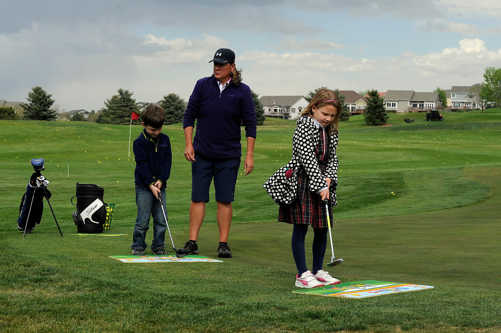 Description of . DENVER, CO - MAY 7: Eva Hellvig, 7, right, and Cameron Fay, 6, practice a putting motion during their first class with Nina Krats, center, at Foothills Golf Course on May 7, 2014, in Denver, Colorado. Foothills Park and Recreation is aiming to increase participation in its golf programs, especially in regards to youth involvement. (Photo by Anya Semenoff/The Denver Post)