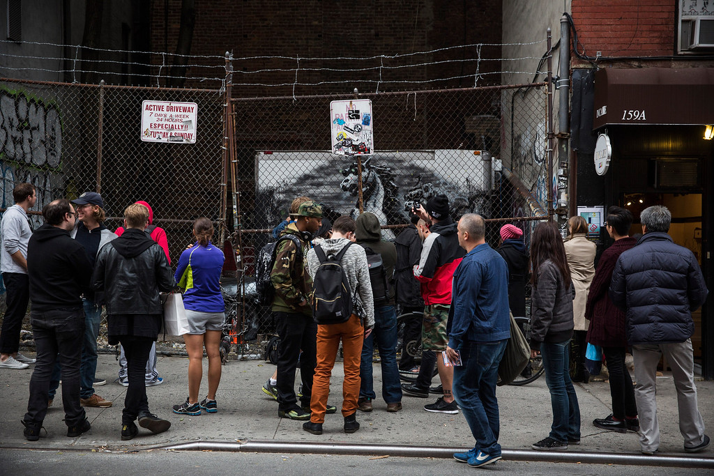 Description of . People look at the latest work from street artist Banksy  on October 9, 2013 in the Lower East Side neighborhood of New York City. Banksy is in the midst of creating a month long series of pieces of street art.  (Photo by Andrew Burton/Getty Images)