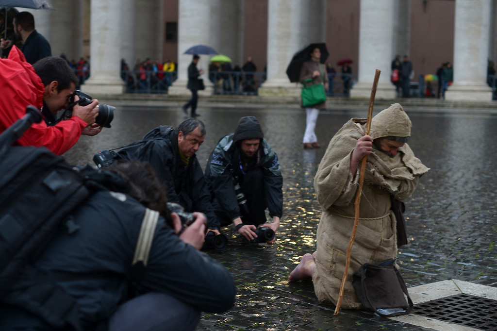 Description of . Photographers take pictures of a barefoot faithful at St Peter\'s square during the conclave on March 12, 2013 at the Vatican.  AFP PHOTO /GABRIEL BOUYS/AFP/Getty Images