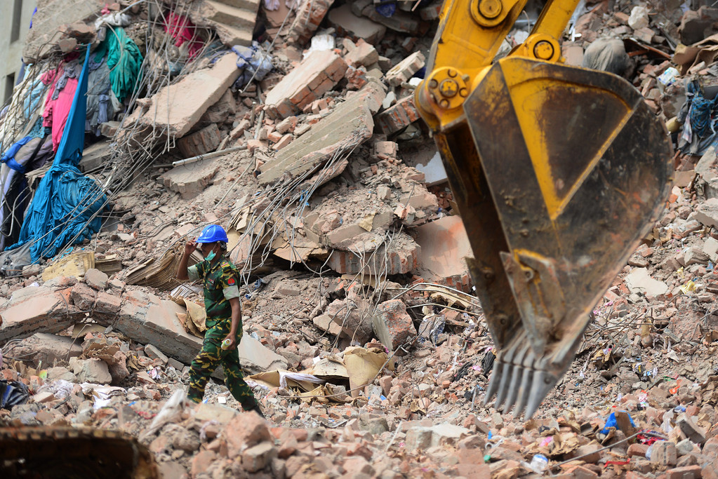 Description of . A member of the Bangladesh Army operates an excavator to remove debris after an eight-storey building collapsed in Savar, on the outskirts of Dhaka, on April 30, 2013.    AFP PHOTO/MUNIR UZ ZAMAN/AFP/Getty Images