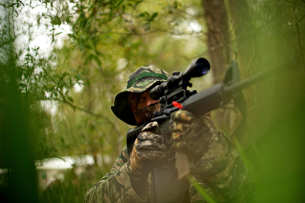 ". A member of the North Florida Survival Group raises his AR-15 rifle as he joins other members in performing enemy contact drills during a field training exercise in Old Town, Florida, December 8, 2012. The group trains children and adults alike to handle weapons and survive in the wild. The group passionately supports the right of U.S. citizens to bear arms and its website states that it aims to teach ""patriots to survive in order to protect and defend our Constitution against all enemy threats\"". Picture taken December 8, 2013.   REUTERS/Brian Blanco"