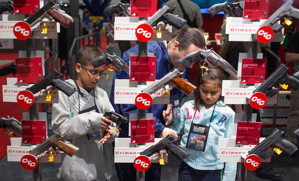 Description of . Family members look at hand guns at the George R. Brown Convention Center, the site for the National Rifle Association's annual meeting in Houston, Texas on May 4, 2013. Organizers expect some 70,000 attendees at the 142nd NRA Annual Meetings & Exhibits in Houston, which began on Friday and continues through Sunday. REUTERS/Adrees Latif