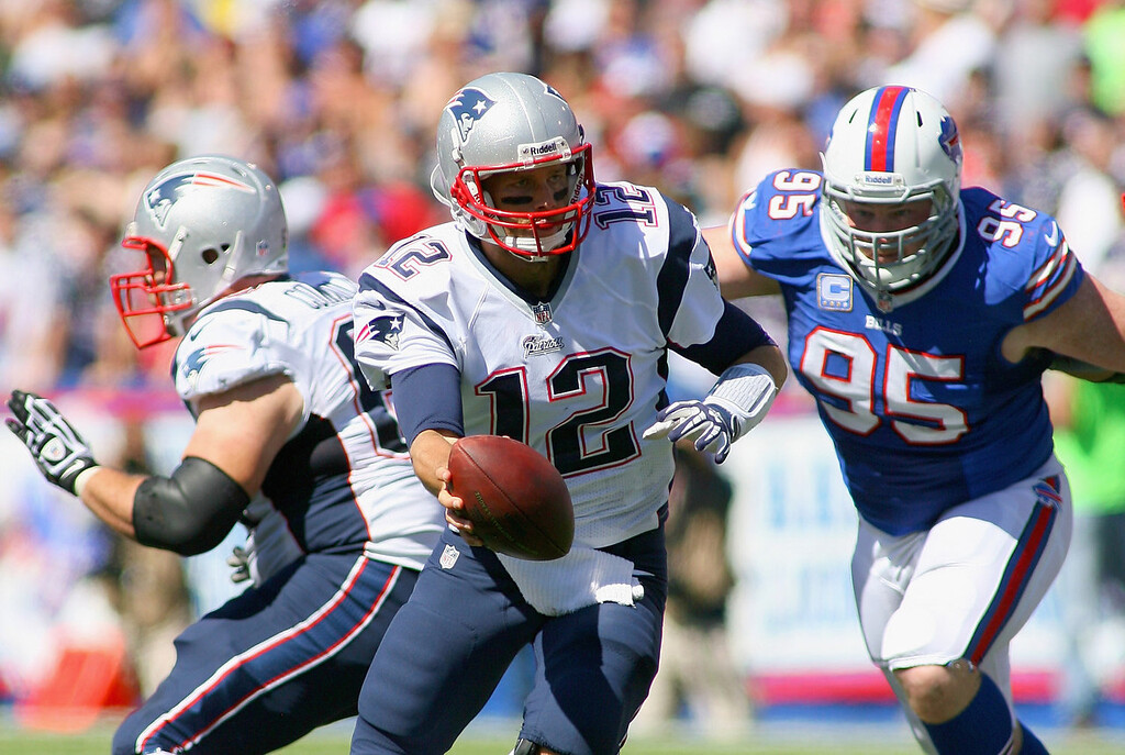 Description of . Tom Brady #12 of the New England Patriots readies to hand off with pressure from  Kyle Williams #95 of the Buffalo Bills at Ralph Wilson Stadium on September 8, 2013 in Orchard Park, New York.  (Photo by Rick Stewart/Getty Images)